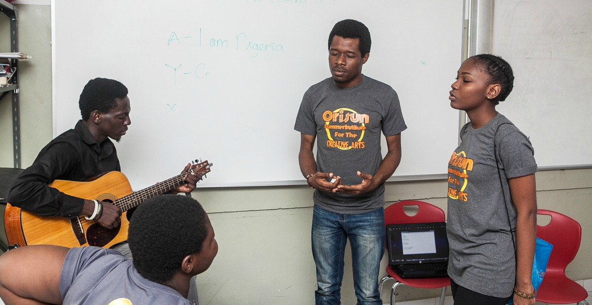 Edward working with GUITARIST AND osica students during singing class.