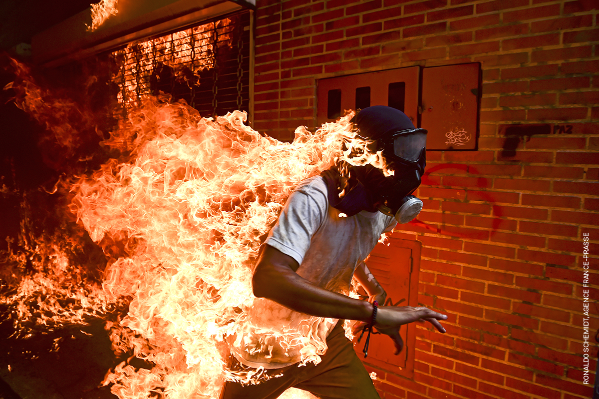 3 May 2017  José Víctor Salazar Balza (28) catches fire amid violent clashes with riot police during a protest against President Nicolas Maduro, in Caracas, Venezuela.