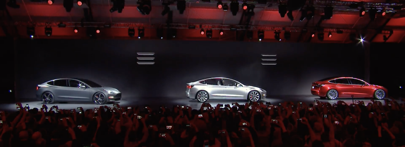 To great applause, three new Tesla Model 3's drive onto the stage