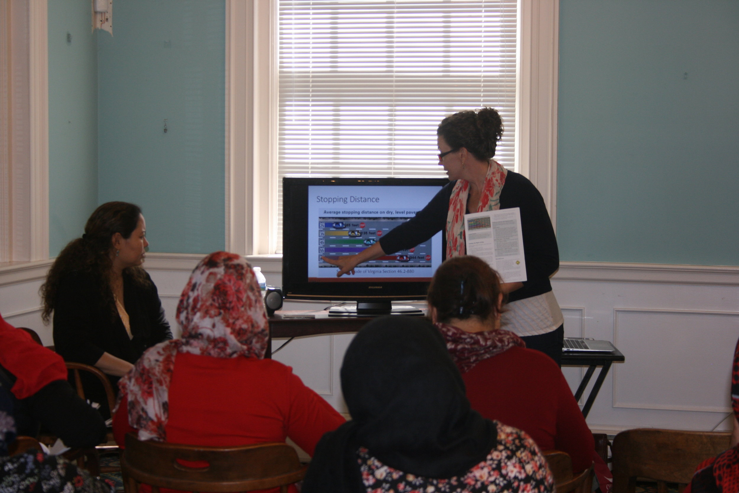 Outreach Coordinator Laura Jones instructs the class on the rules of the road with the help of an interpreter.