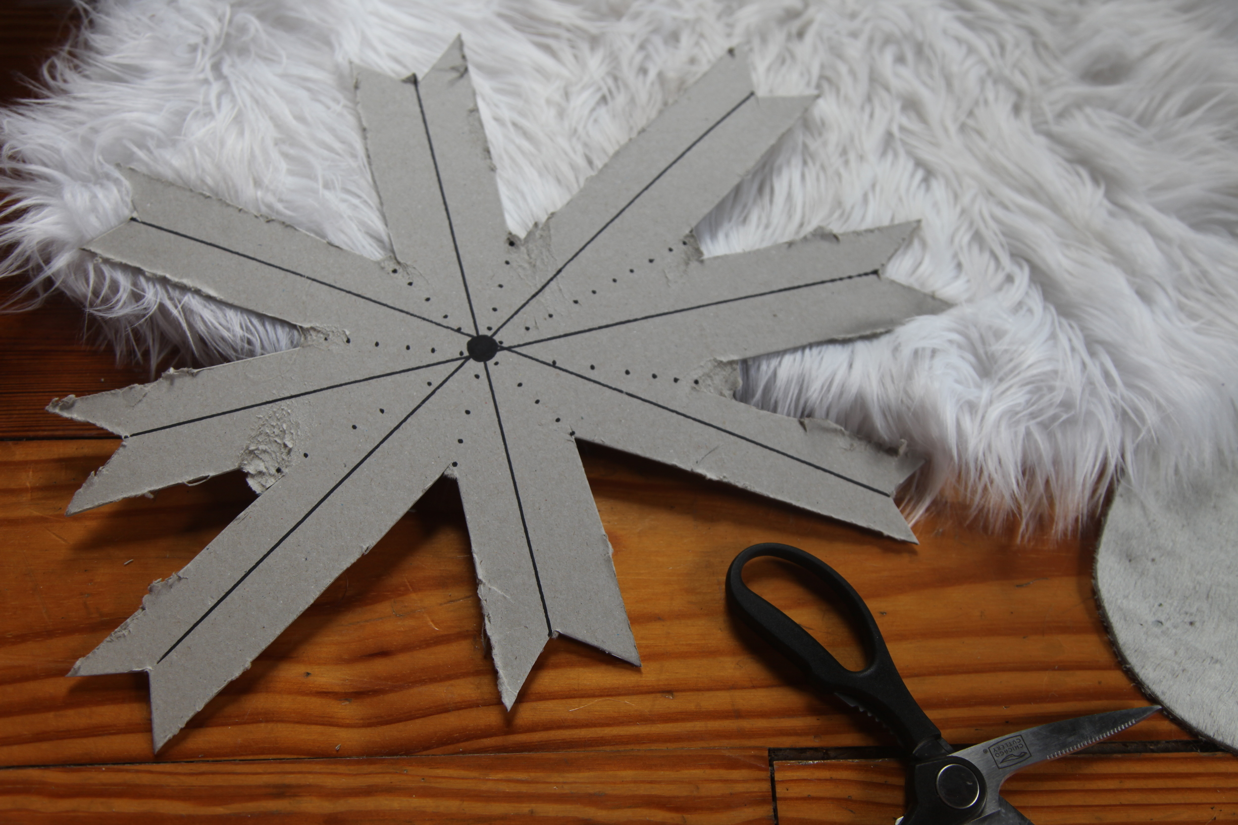 """Step Two: Create an Outline  Your cardboard cutout lines should resemble that of a compass. Start by drawing a cross with lines going North, South, East, and West then Northeast, Northwest, Southeast, and Southwest. These lines will be your center points on your 8 arrows.  Draw dotted lines between each arrow, these will be your valley points and will help with cutting. Don't stress if your lines or cuts don't end up perfect, the matchsticks will hide all of it. It is really just a guideline and extra support that makes the creating process a little bit easier. I made each arrow around 2"""" thick and 7"""" long, some will be longer and some shorter so I kept the extra length just to be safe."""