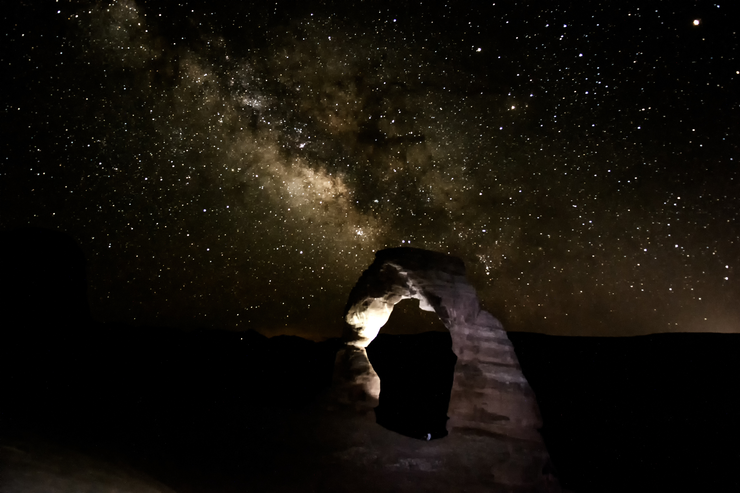 6/26 Photo: Delicate Arch with the Milky Way behind it. That tiny white dot in the middle is a person, just to give some perspective! It was truly incredible to sit on top of a mountain in the desert so late at night and hike out by headlamp.