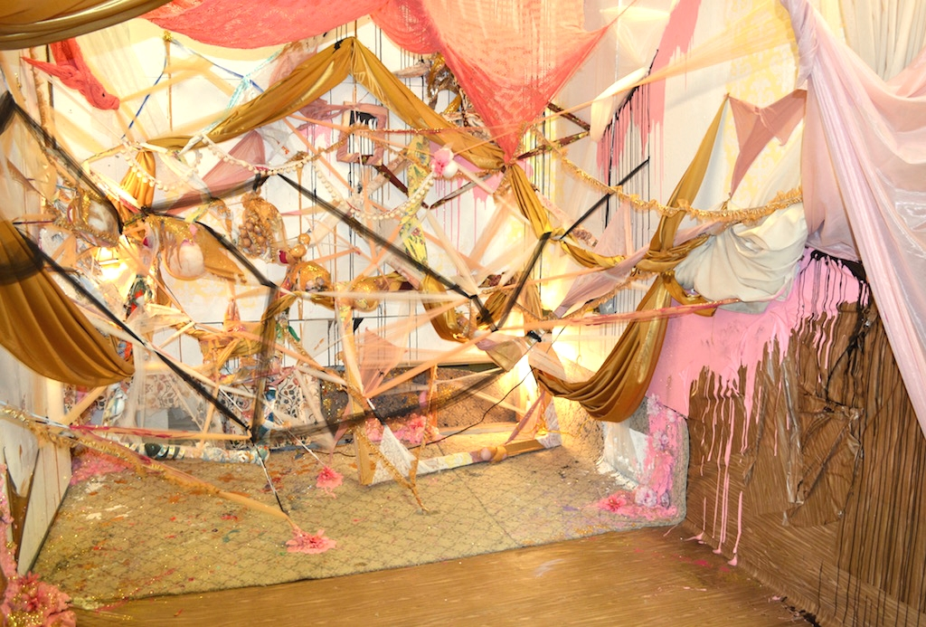 2015,  Spun Out   Studio installation 10'X10'x10'. Tulle, synthetic silk, lace, faux-wood adhesive contact paper, rug, fake flowers, glitter, house paint, acrylic paint, stretcher bars, curtains, spray foam insulation.
