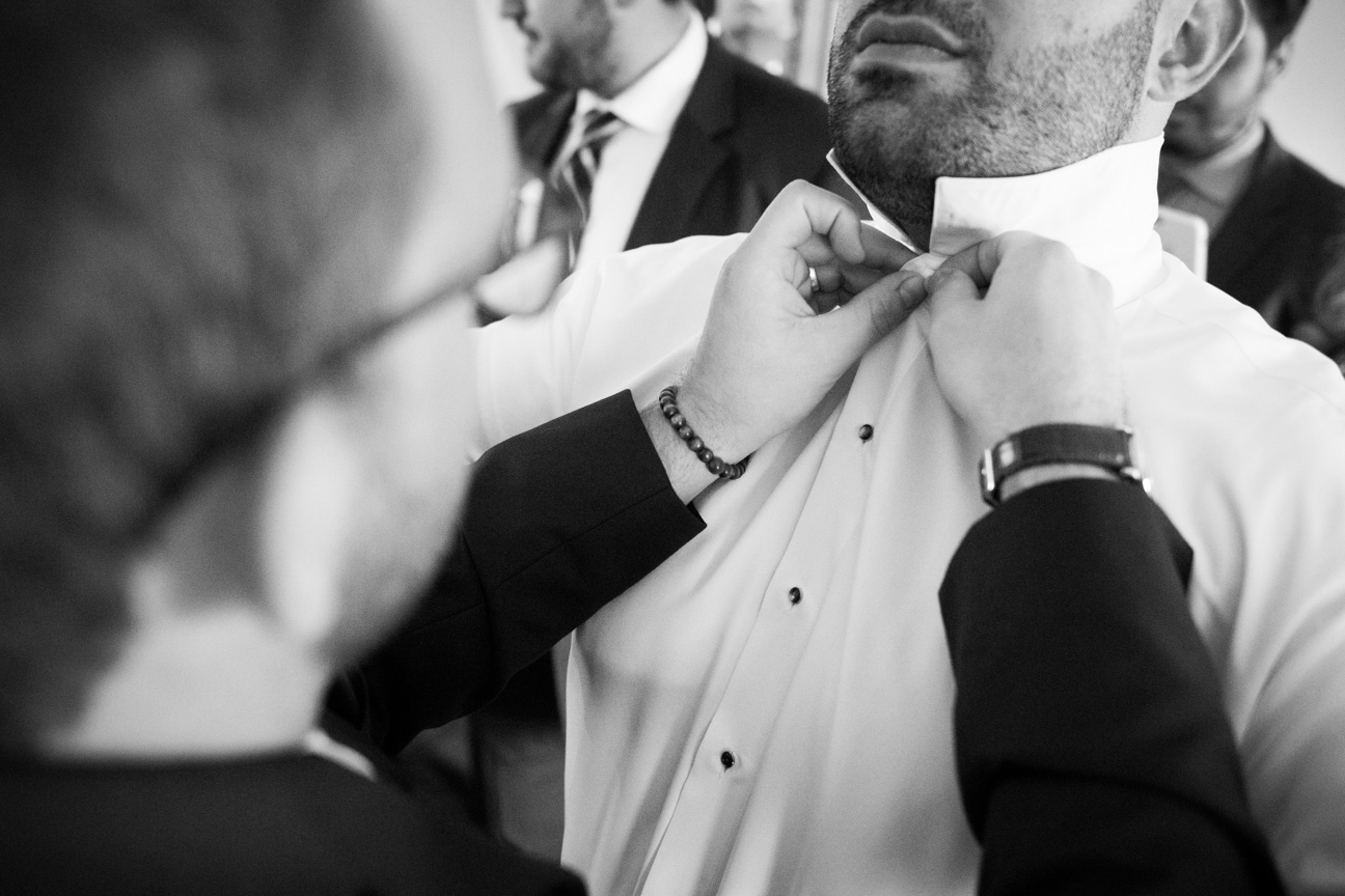 Groomsman helping the Groom button his shirt