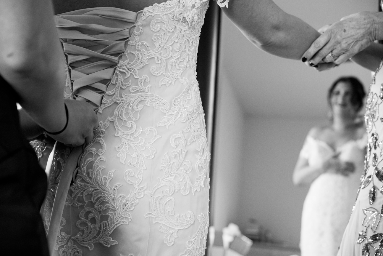 Bride getting wedding dress laced