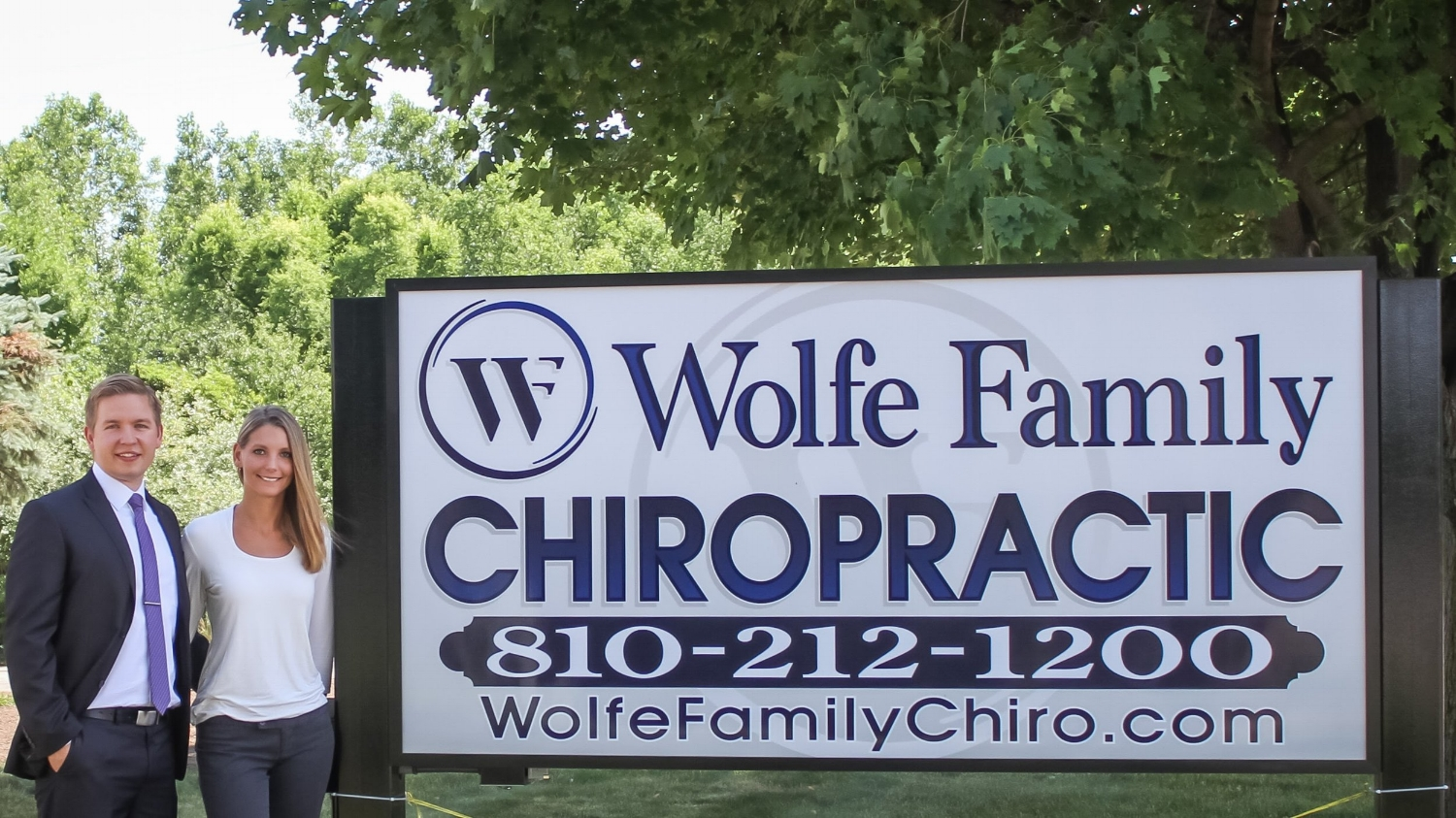 Dr. Alex Wolfe & Dr. Hannah Wolfe by the Wolfe Family Chiropractic sign on Dryden Rd. in Metamora, MI