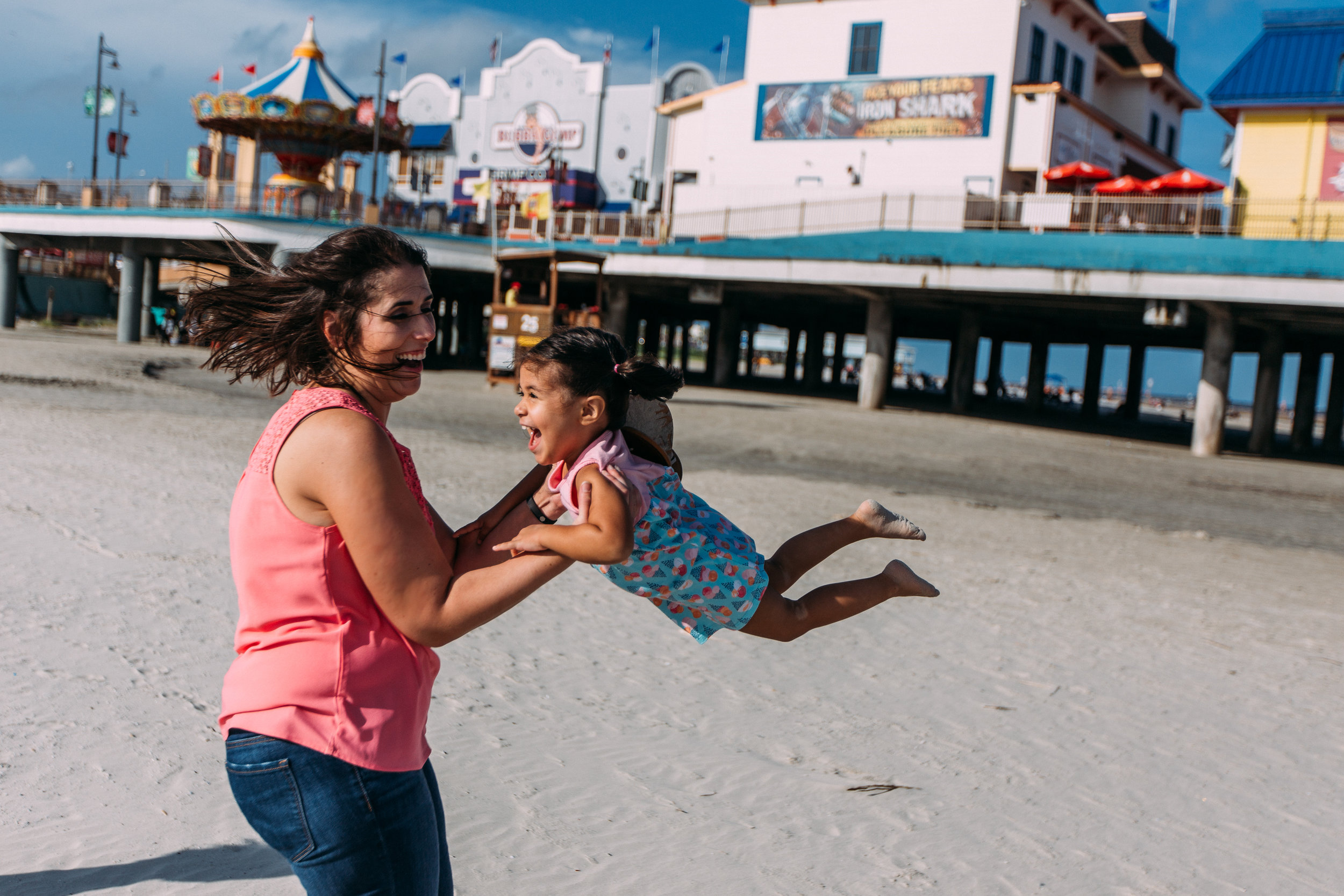 Mother and daughter spinning on the beach