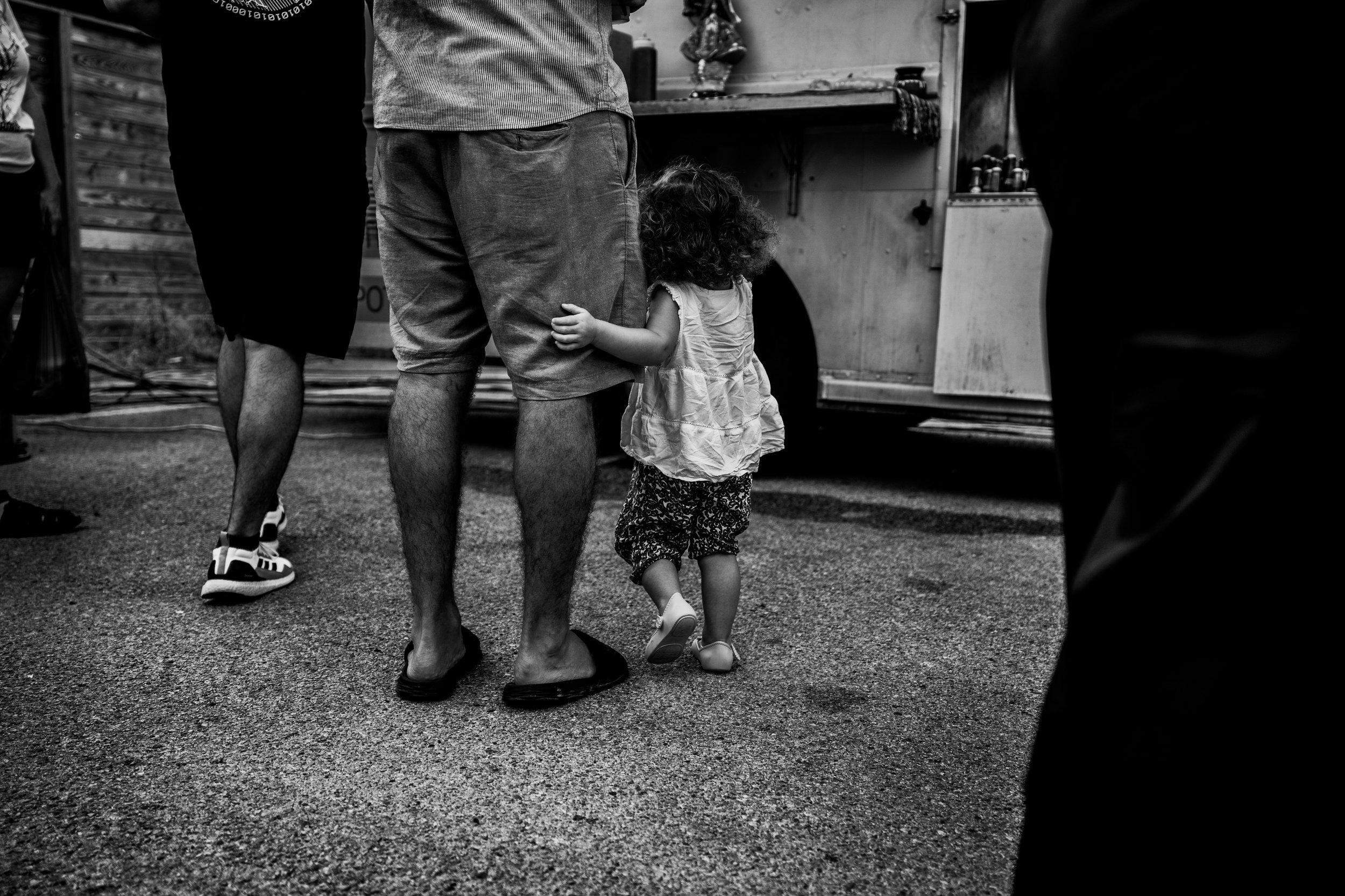 Little girl hugging her daddy's leg