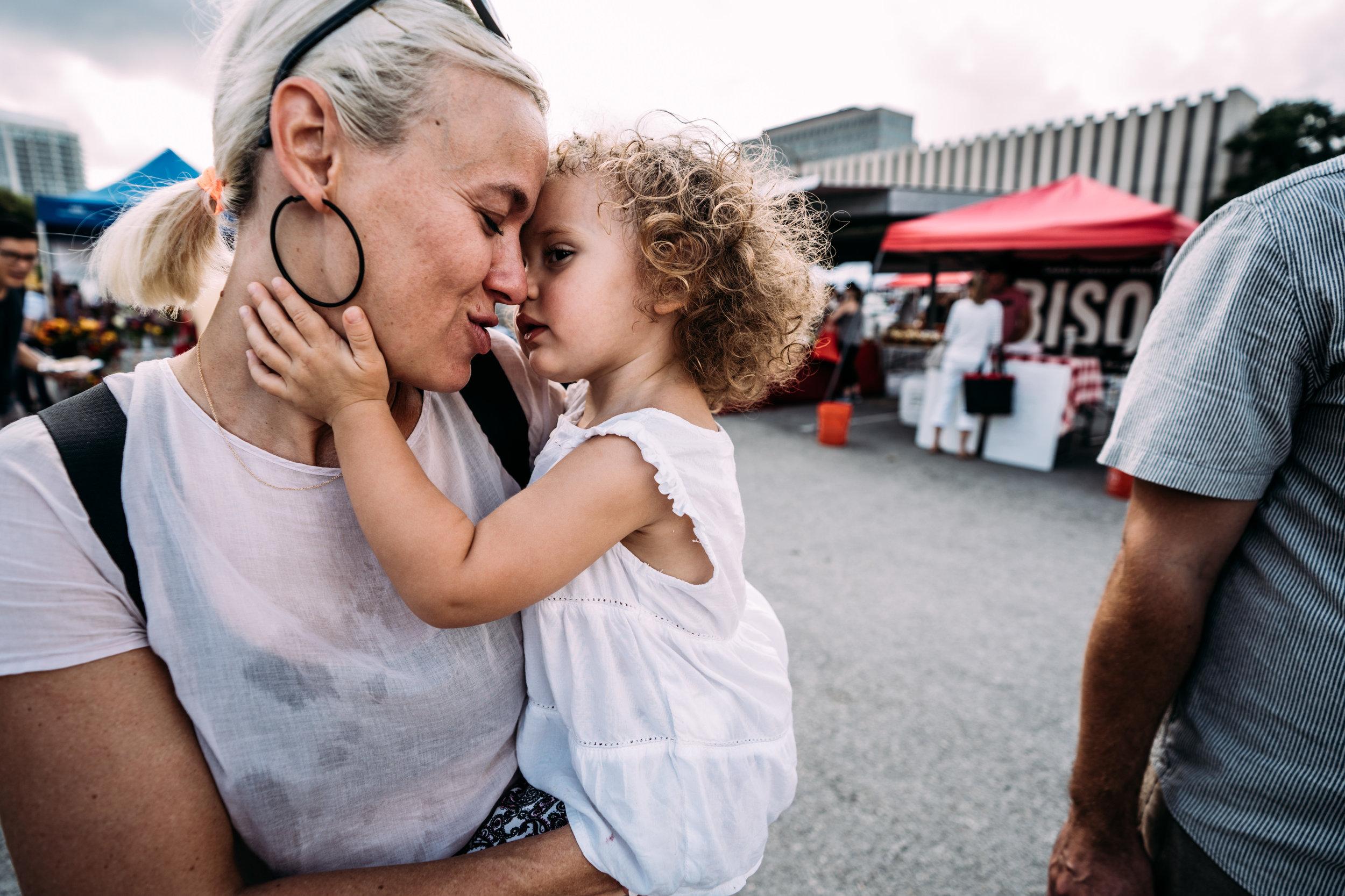 Little girl caresses her mom's face.