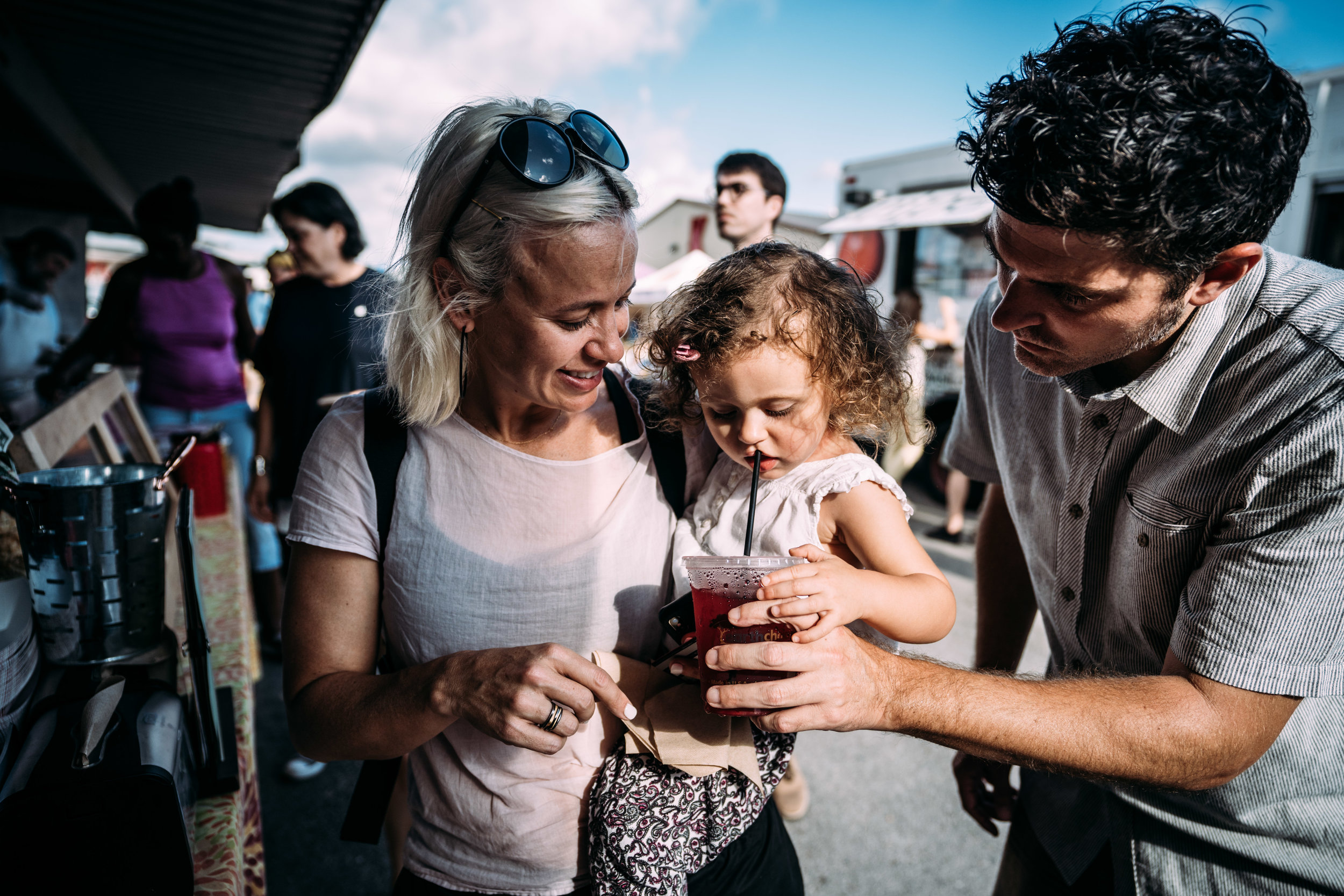 Dad gives little girl a drink while mom holds her