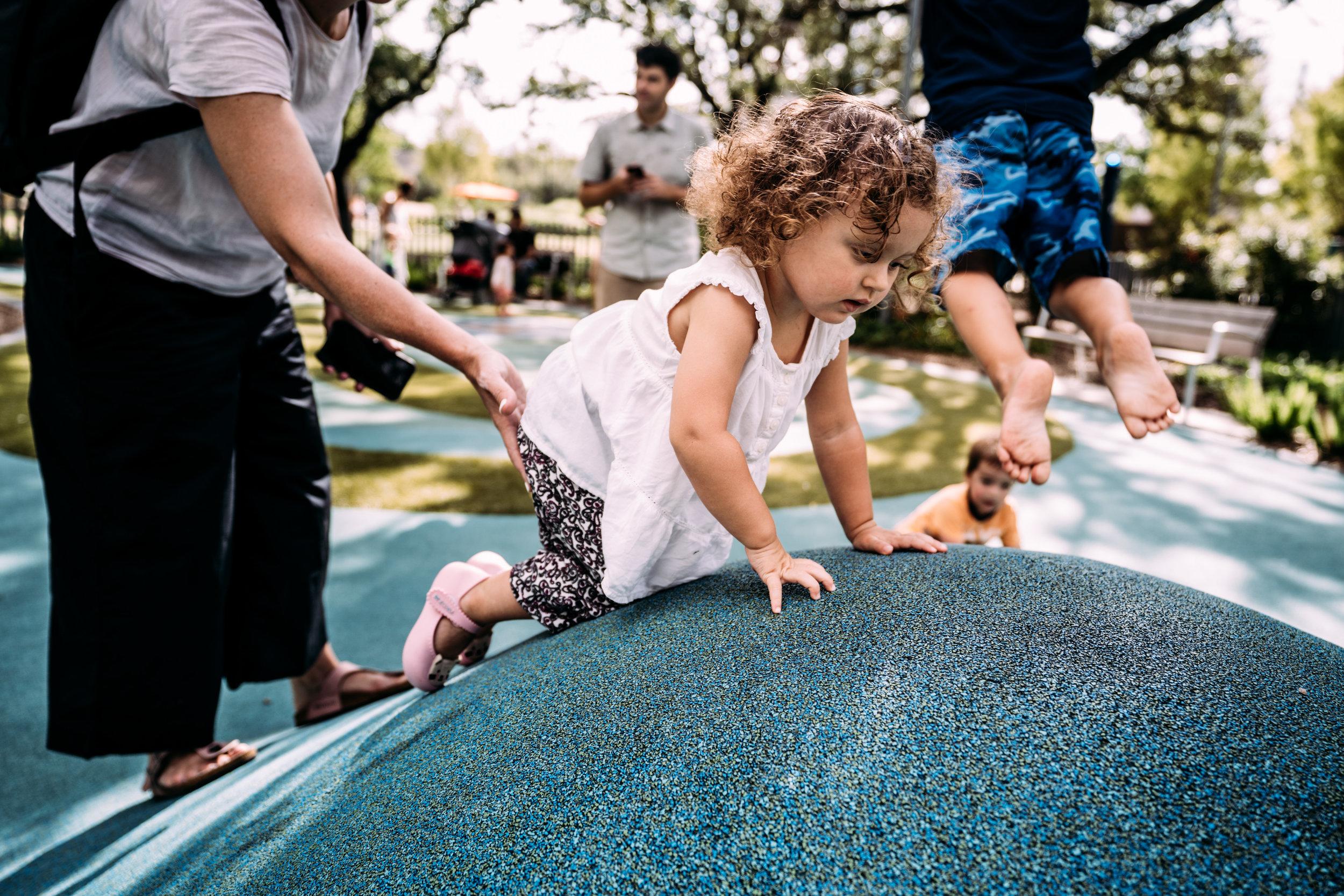 Little girl climbs a hill at levy park