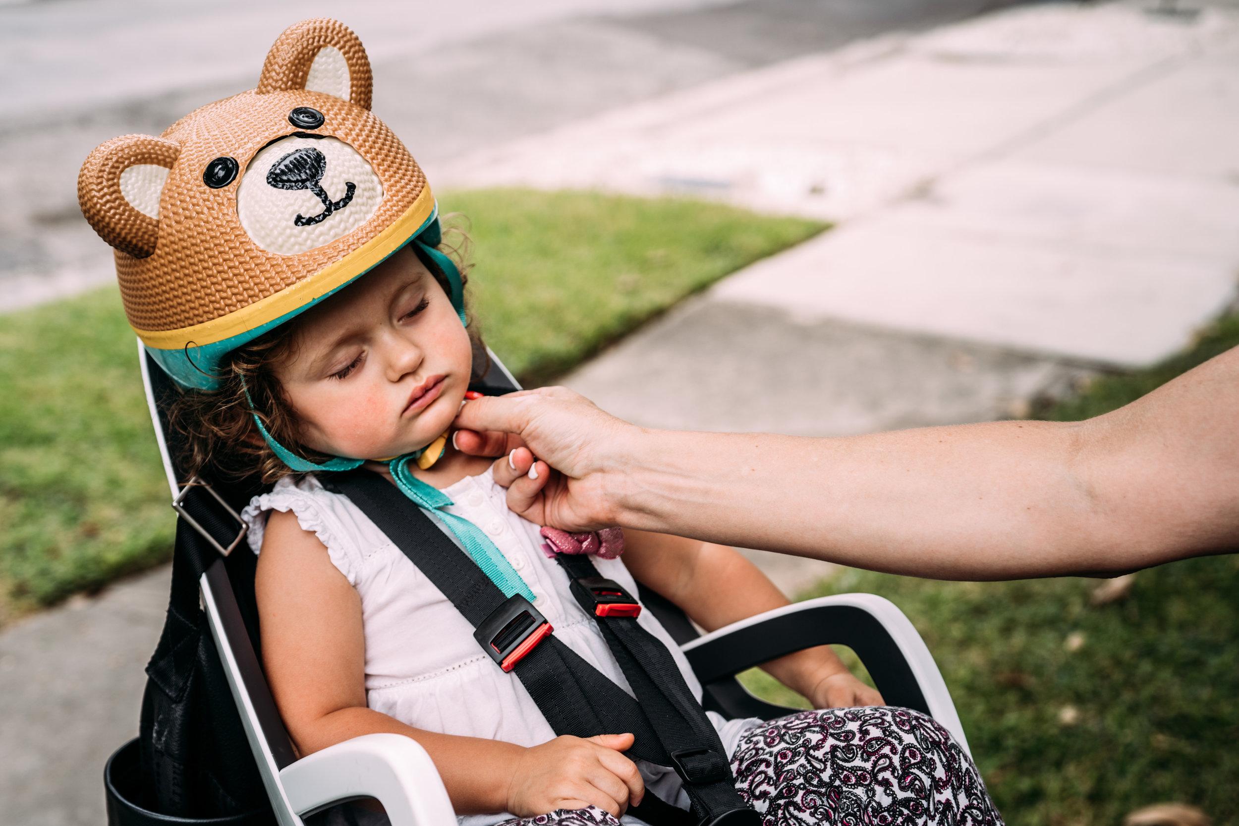 Little girl fell asleep in her bike helmet