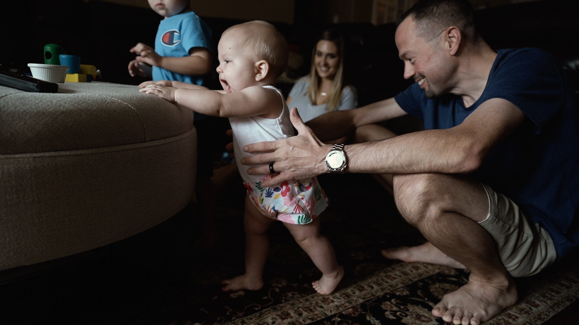 baby stands while dad assists