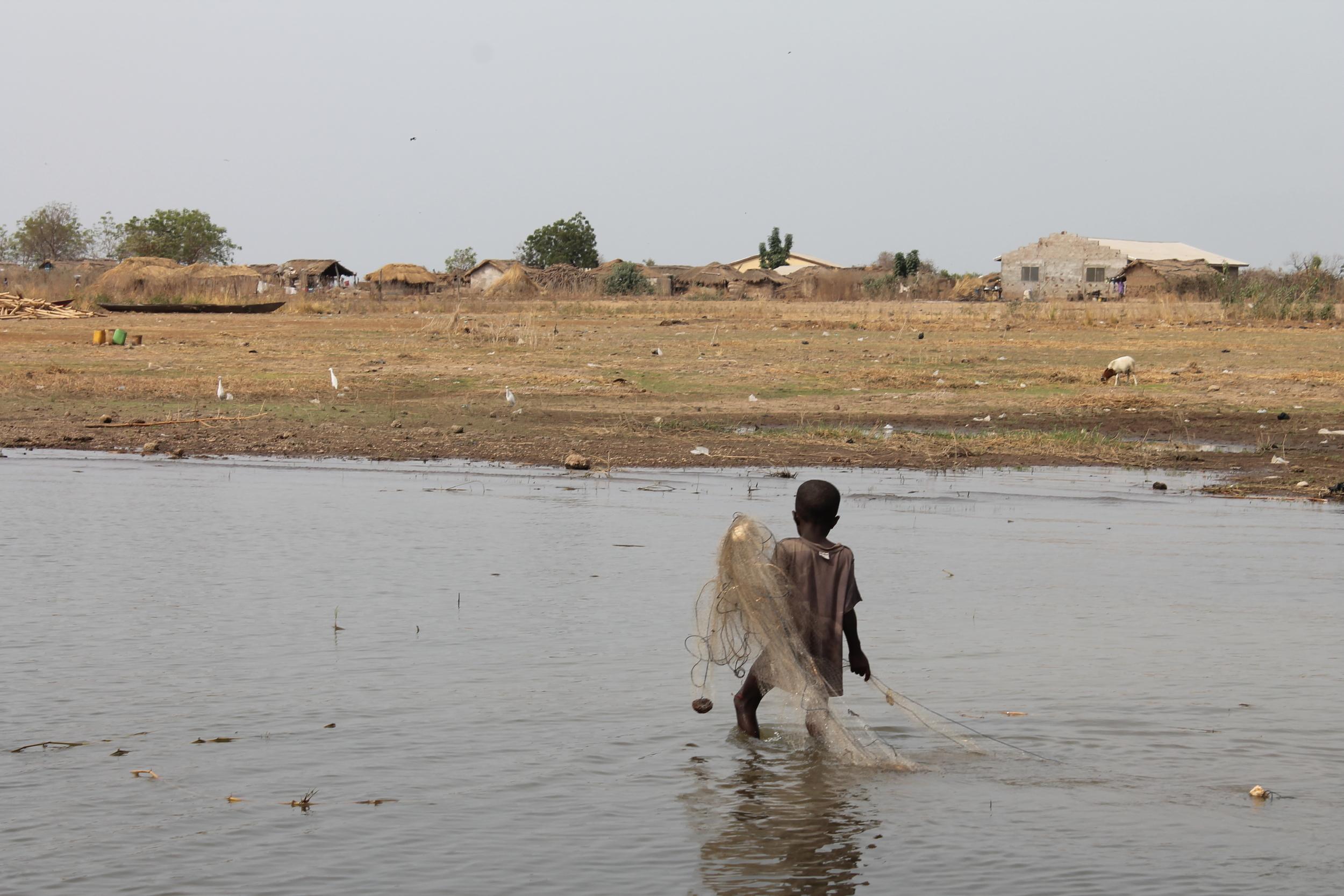 A small boy hoists a fishing net on Lake Volta