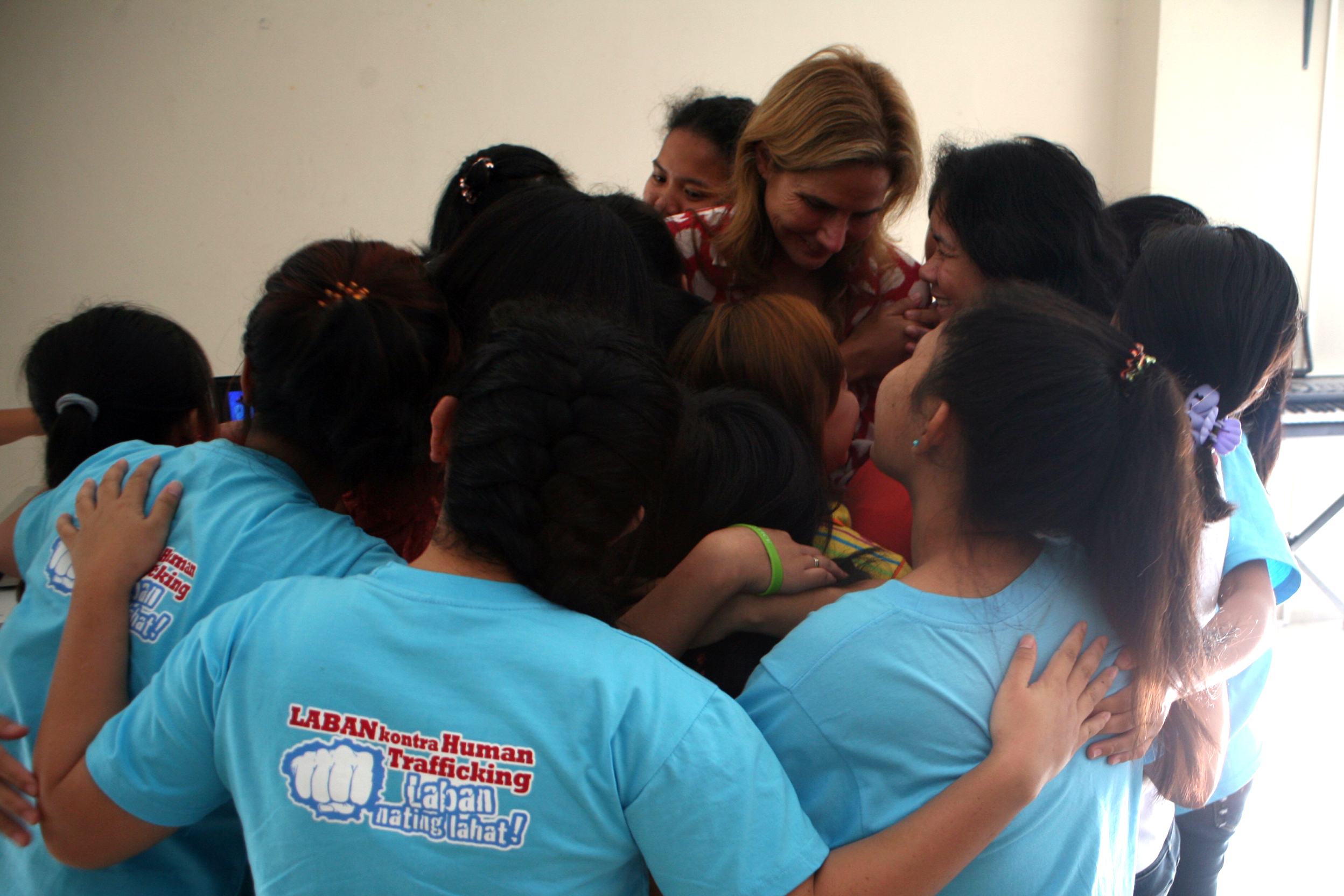 Children trafficking survivors crowd around and embrace