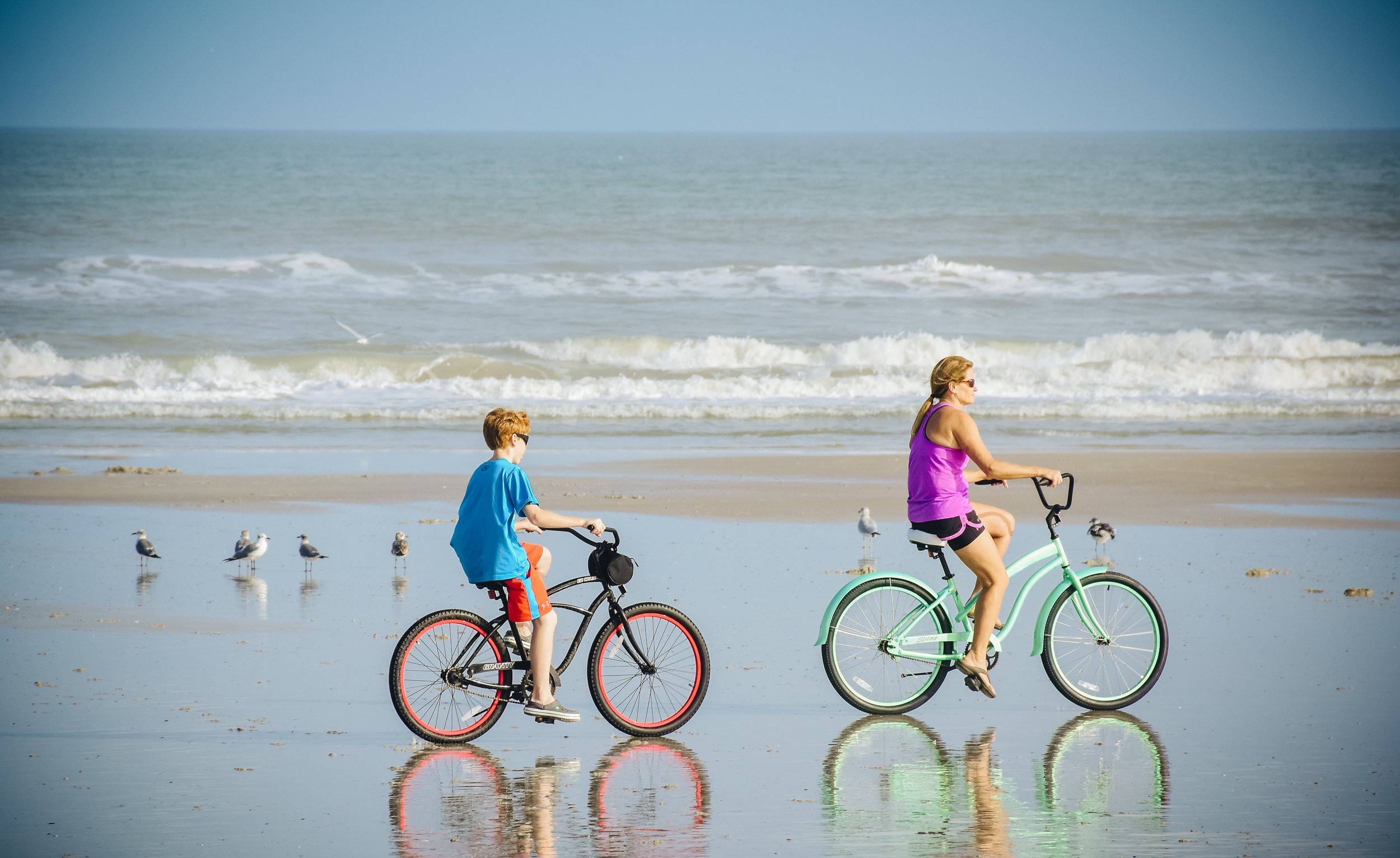 A mother and son cycled leisurely along the shore in Jacksonville, FL.