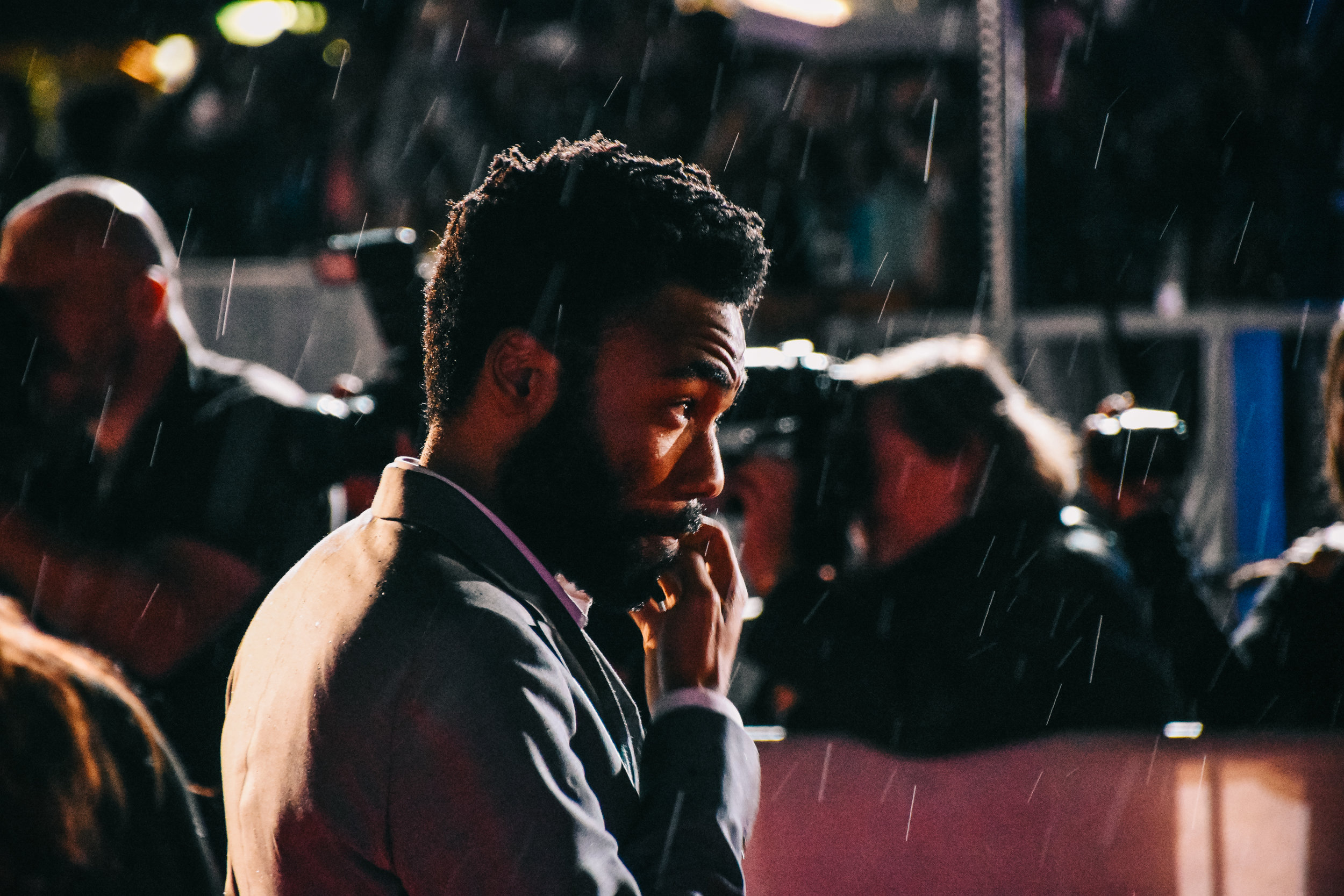 Donald Glover waits in the rain on the red carpet.