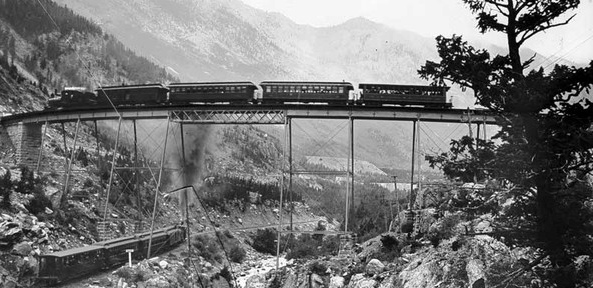 A historic black and white photo of the Georgetown Loop high bridge. One train crosses over the bridge while another crosses underneath it.