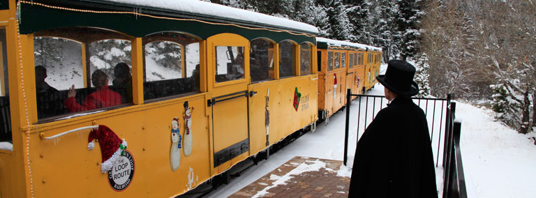 A photo of the coach cars in a bright yellow hue decorated for the holiday season. Winter Wonderland tours and Santa's North Pole Adventure trains are very popular throughout the holiday season. The ticket master stands to the right of the train watching as it pulls away.