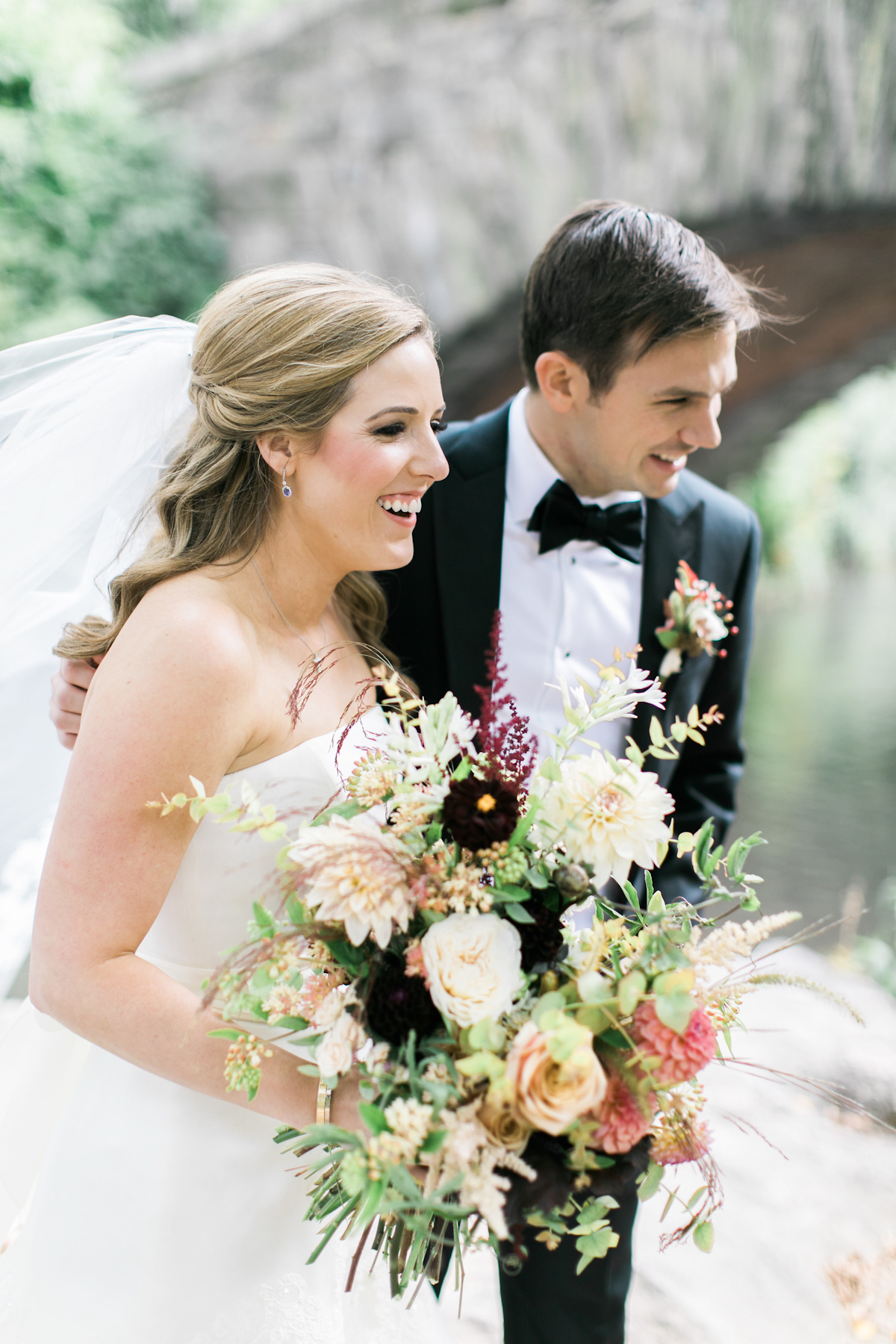 Groom and bride holding bouquet in Central Park