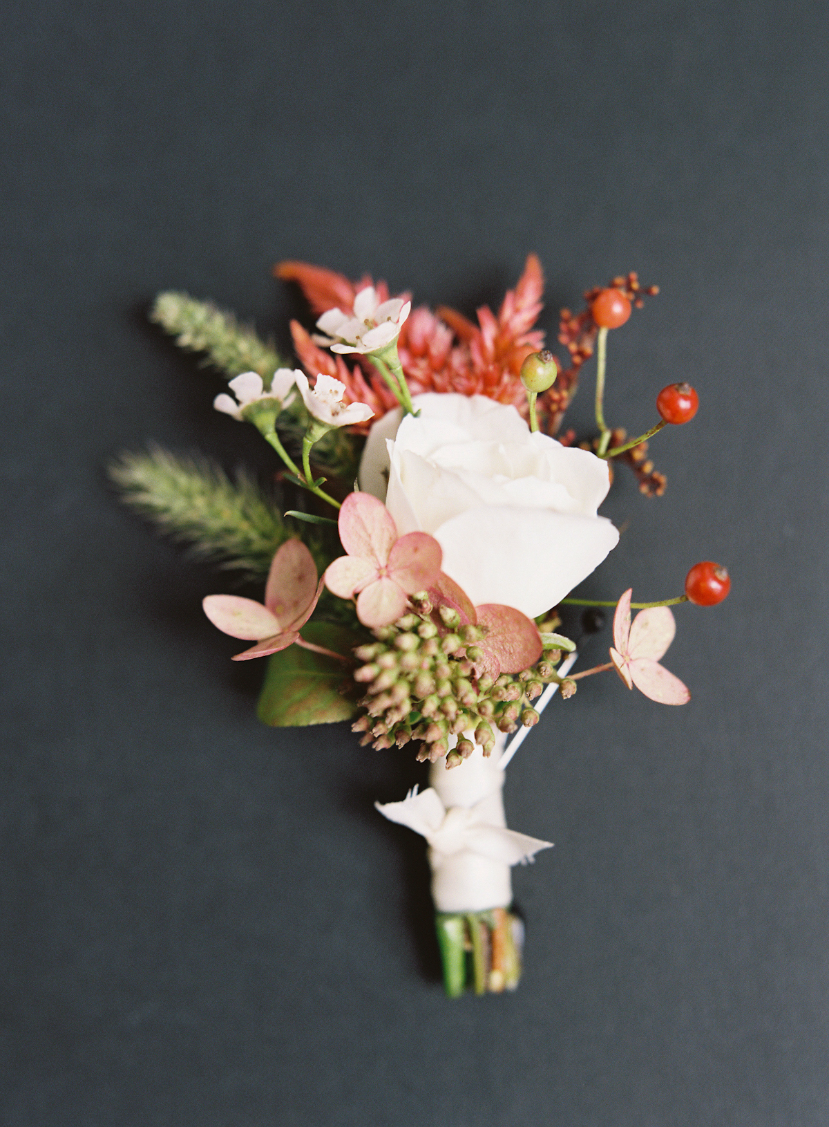 Plaza wedding boutonniere with rose and red berries