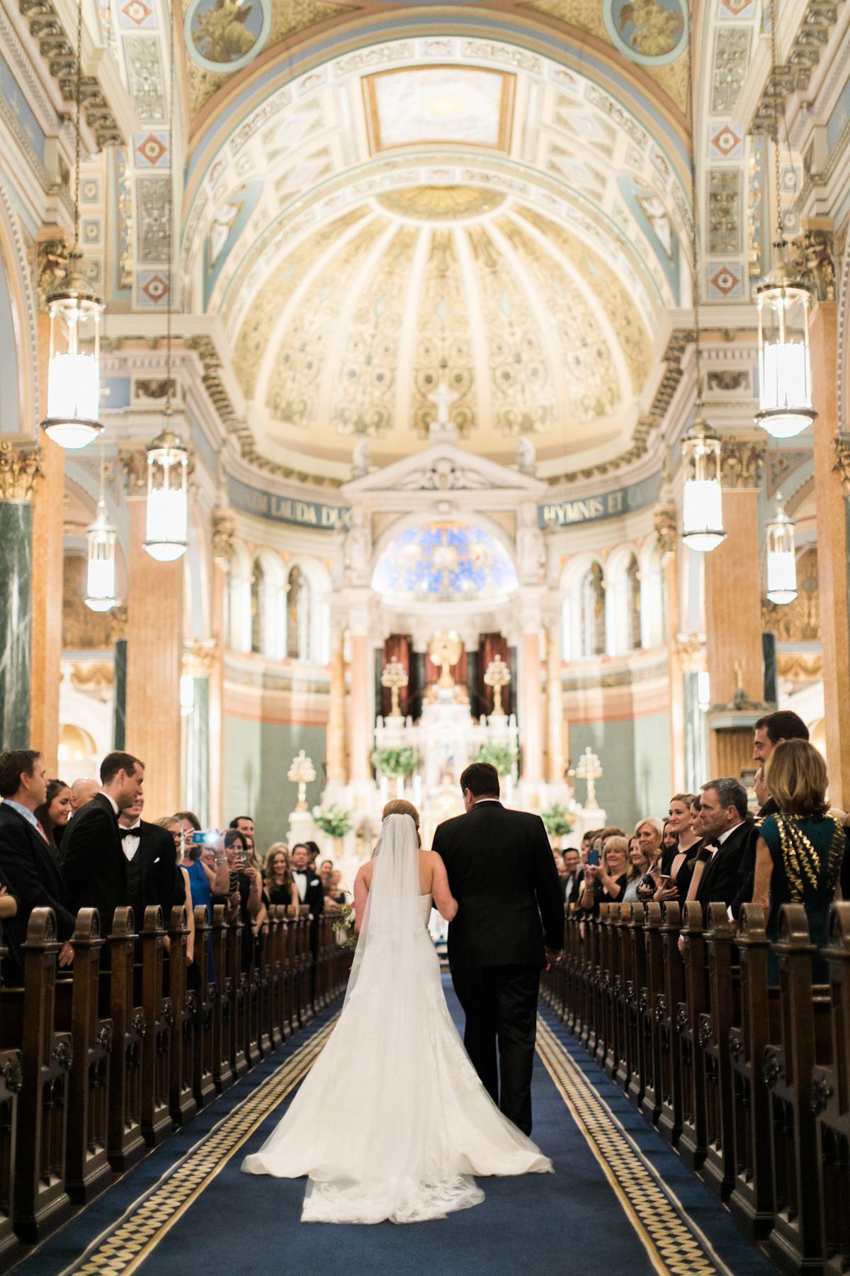 Bride walking down the aisle at St Jean Baptiste Church
