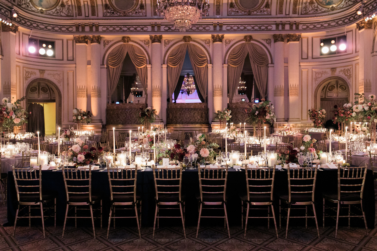 Plaza wedding long tablescape with lush flowers and taper candles