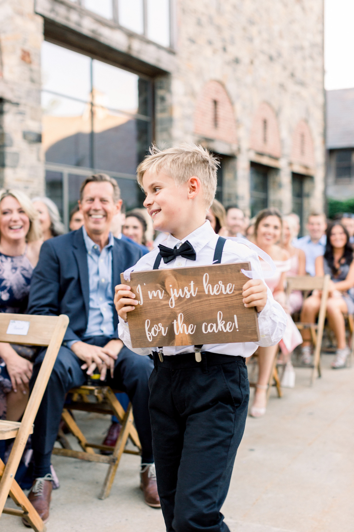 Ring bearer holding wooden sign at Blue Hill at Stone Barns wedding