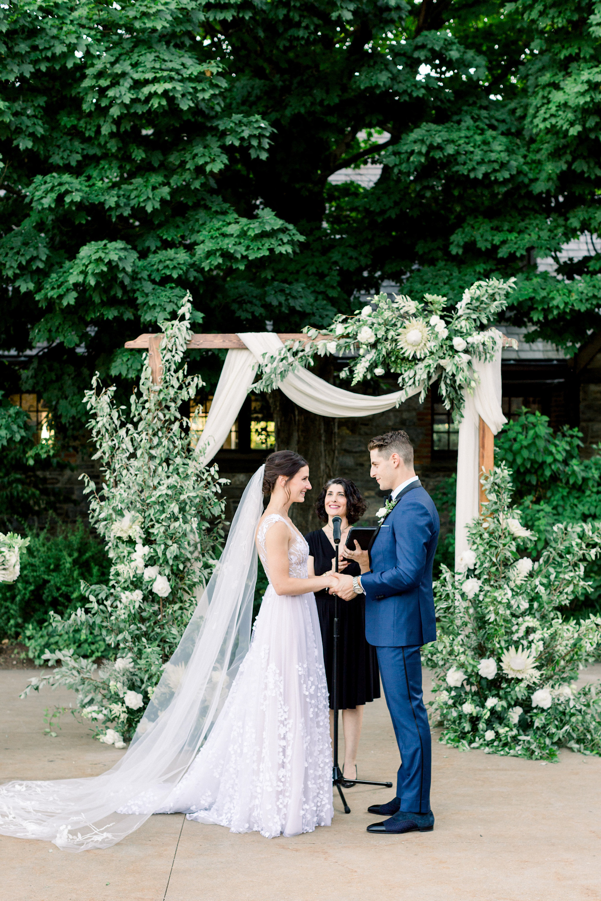 Bride and groom in front of floral arch at Blue Hill at Stone Barns wedding