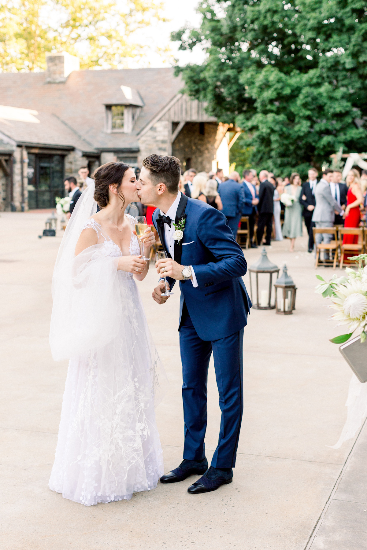 Bride and groom kissing with champagne at Blue Hill at Stone Barns wedding
