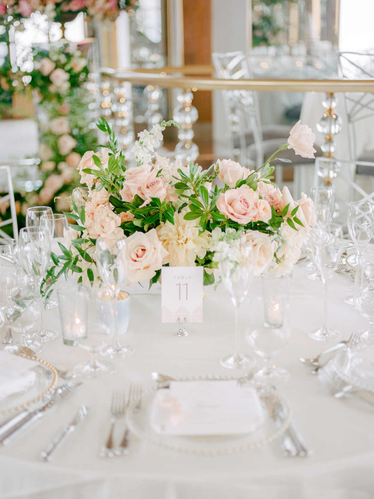 Rainbow Room wedding tablescape with flowers, votives, menus and vellum place cards