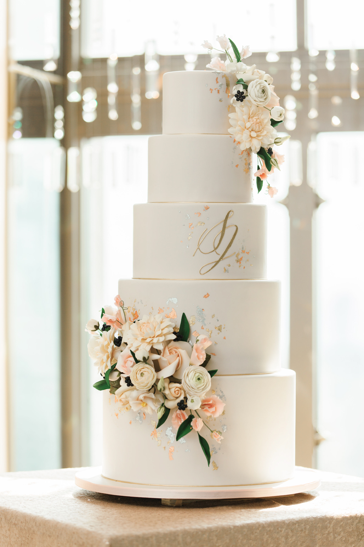 Wedding cake with flowers and metallic accents at Rainbow Room wedding