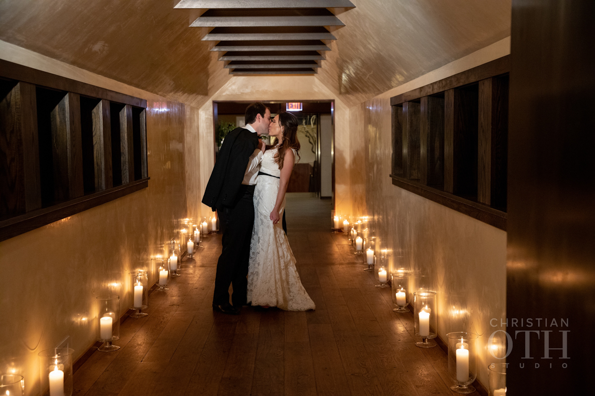 Bride and groom kissing in a hallway flooded with candlelight at Blue Hill at Stone Barns