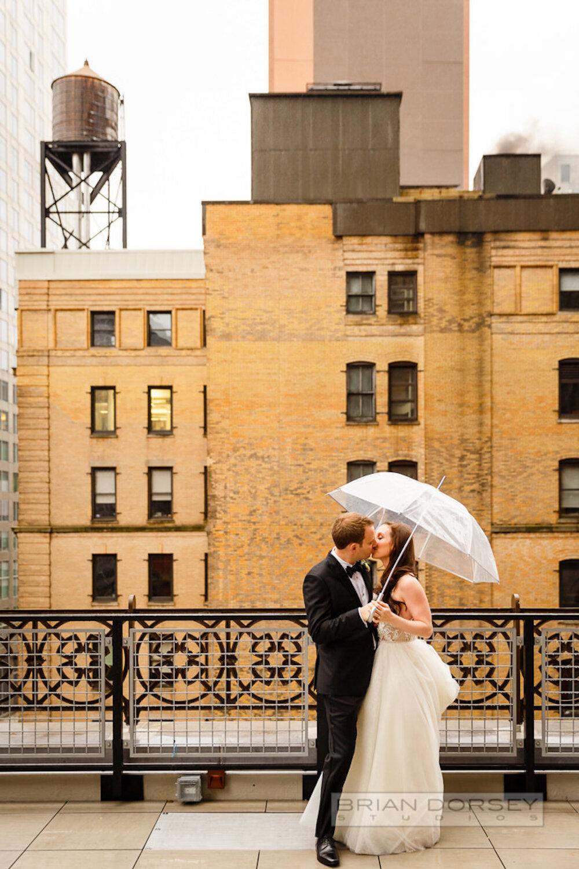 Rooftop bride and groom under umbrella