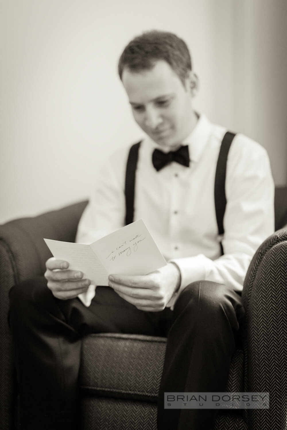 Groom in black tie reading a card on his wedding day