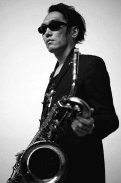 """吉田隆一(b.sax)  1971年生まれ、東京都出身。バリトンサックス奏者、作曲家、文筆家。  中学校の吹奏楽部でバリトンサックスを手にする。 91年よりプロとしての活動を開始。数々のミュージシャン、表現者との共演を重ね、多くのレコーディング、「渋さ知らズ」を始めとするバンドでのヨーロッパツアーに参加、国内外での公演を行う。  現在、芳垣安洋(ds)「MoGoToYoYo」、林栄一(as)「Gatos Meeting」、板橋文夫(p)グループ、巻上公一(composer&producer)「ゴジラ伝説」などにメンバーとして参加。  2005年、""""SF+フリージャズ""""をテーマにしたリーダーバンド『blacksheep』をスガダイロー(p)、後藤篤(tb)と共に結成。2008年doubt musicよりアルバム『blacksheep/blacksheep』、2011年『blacksheep/2』をリリース。 2013年 VELVETSUN PRODUCTSより『blacksheep/ ∞ -メビウス-』、その後メンバーチェンジを経て2015年『blacksheep/ +Beast』をリリース。 SF作家 神林長平、『機動戦士ガンダム』などのガンダムシリーズ、『伝説巨神イデオン』で知られるアニメ原作・監督 富野由悠季ら著名人からの帯コメントや、漫画家・映像作家 西島大介によるアルバムジャケットが一部で話題となる。  2014年 現代音楽作曲家・ピアニストの新垣隆と共に「N/Y」結成。 2015年 アポロサウンズより新垣隆&吉田隆一『N/Y』をリリース。 全国各地での公演を行う。  2017年 大谷能生(as,PC)、安藤暁彦(as,effects)、トオイダイスケ(p,b,org)、池澤龍作(ds)と共に新リーダーバンド「赤い砂漠 -Deserto rosso-」を始動。   極度のSFマニア、アニメマニアとしても知られ、SFマガジンへの寄稿や、谷甲州『航空宇宙軍史・完全版』(ハヤカワ文庫)の巻末解説など執筆活動も積極的に行っている。  2017年 SE作家・デザイナー・イラストレーターである酉島伝法との新ユニット、吉田隆一&酉島伝法より『響生体』を「SONOKA」にて発表予定。   Official Web site: http://yoshidaryuichi.com/  Twitter: https://twitter.com/hi_doi"""