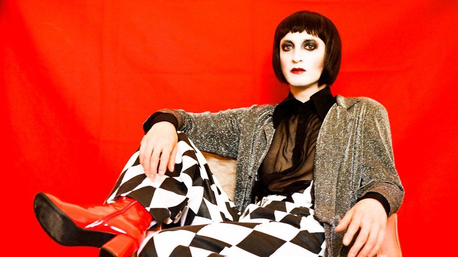 Photo of Art D'ecco, with a brown bob hair cut, glitter shirt, black and white checkered pants, red heels, against a red background.