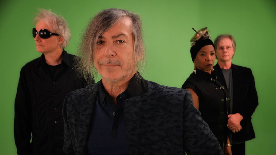 A photo of Simply Saucer: three men with grey hair and black outfits, and one woman with a bronze spaceship on her head. The background is green.