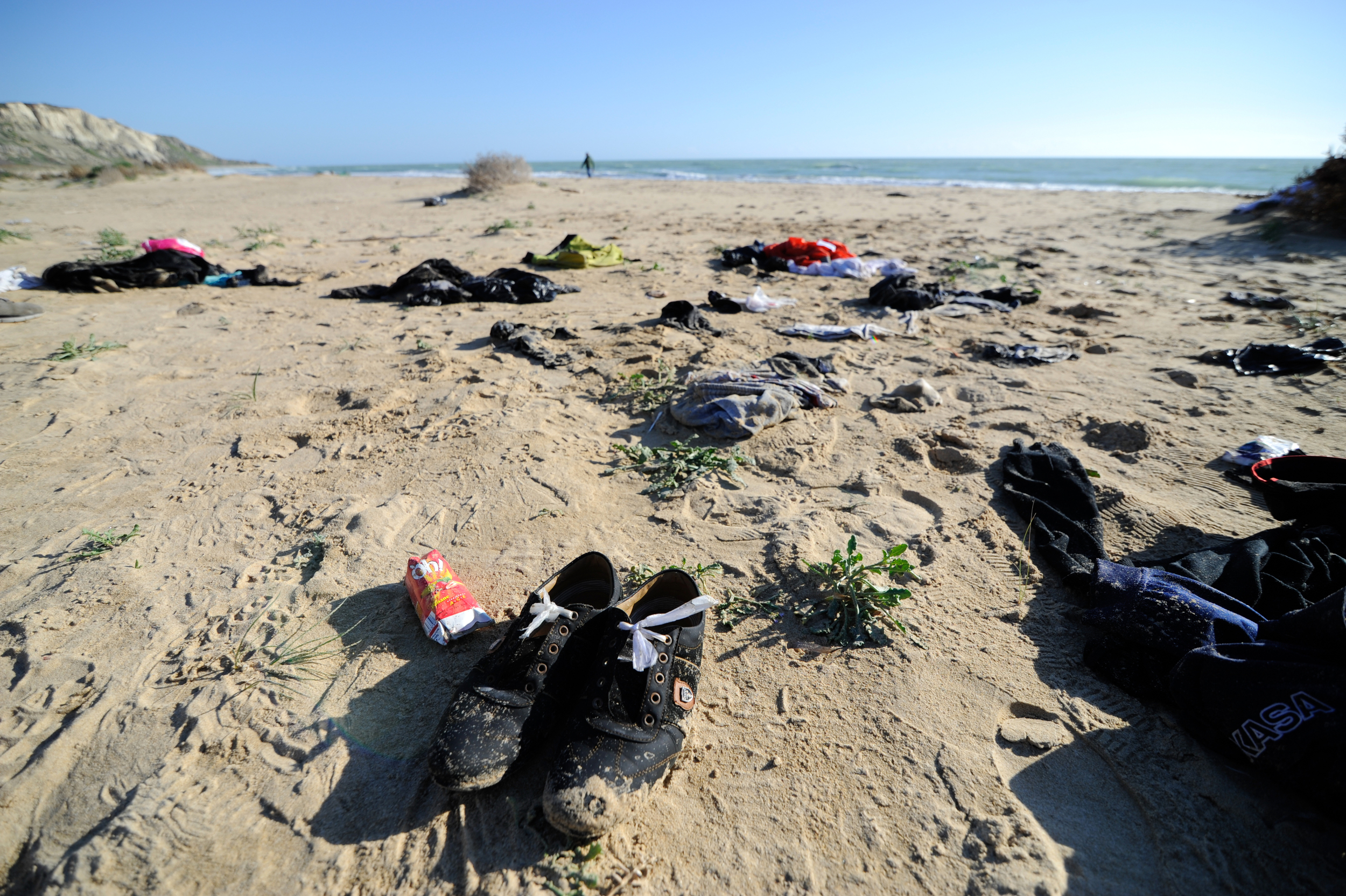 Clothes belonging to migrants lie on the Sicilian beach of Siculiana, Italy February 19, 2016.