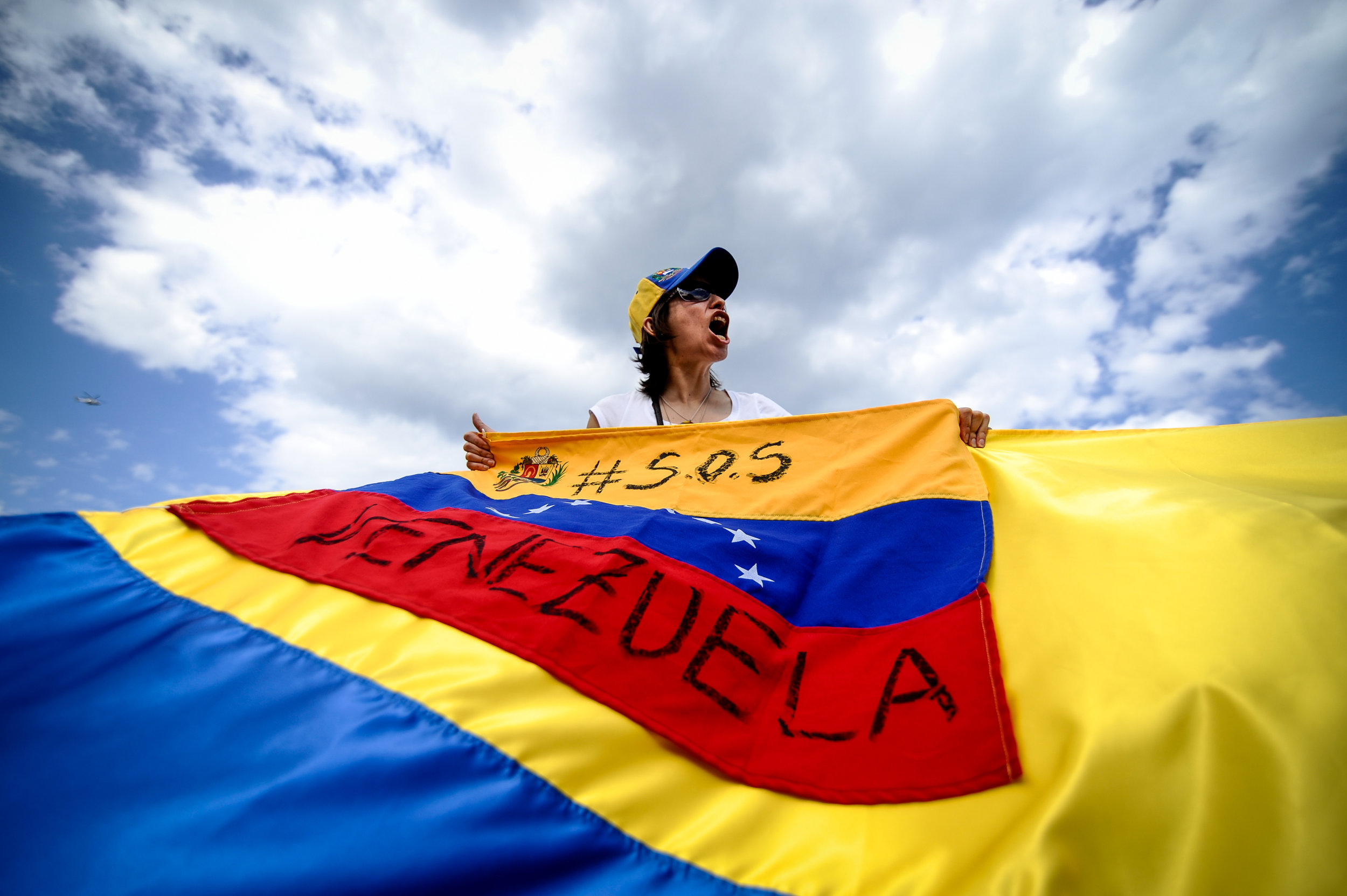 A woman holds a Venezuelan flag as she takes part in a demonstration against the G7 summit in Giardini Naxos near Taormina, Sicily, Italy, May 27, 2017.