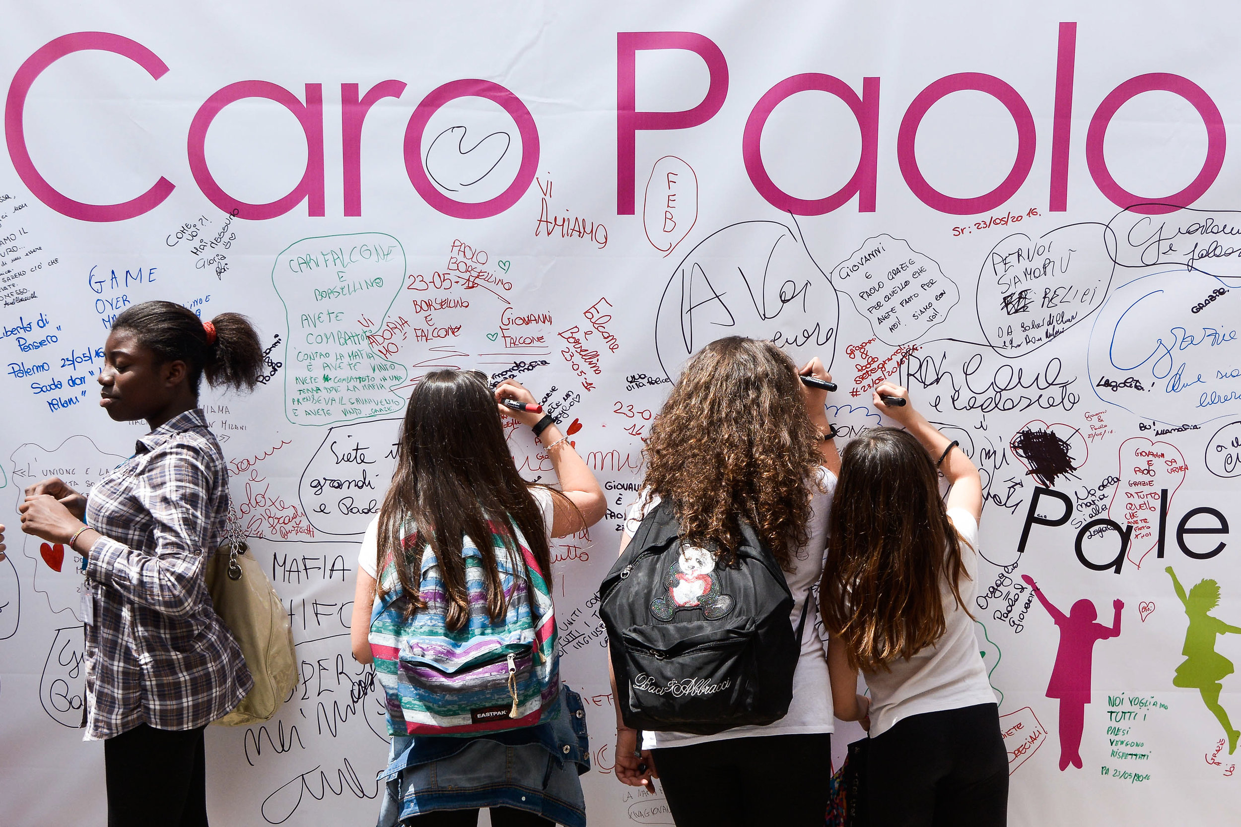 Students write on a banner hung outside the bunker-courthouse of Ucciardone prison to commemorate Judges Paolo Borsellino and Giovanni Falcone in Palermo, southern Italy, May 23, 2016.