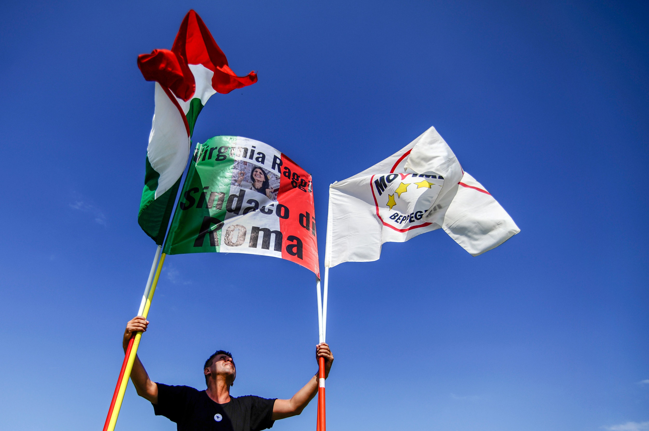 """A 5-Star Movement supporter holds a flag that reads: """"Virginia Raggi Mayor of Rome"""" during a rally in Palermo, southern Italy, September 24, 2016."""
