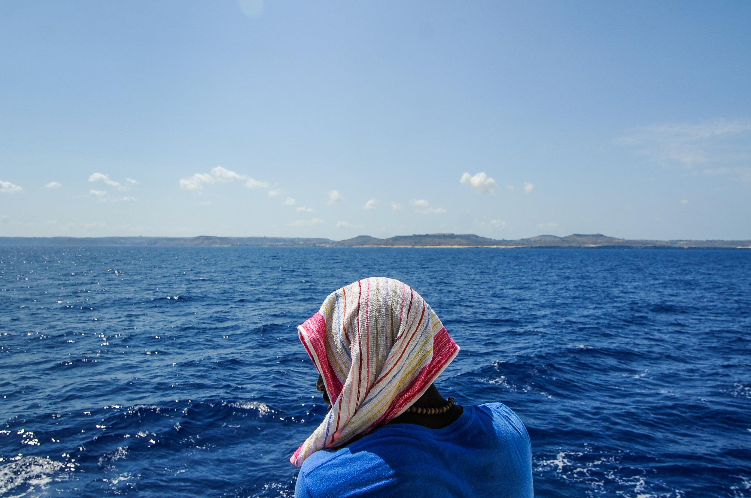 A migrant is seen on board the MV Aquarius as the rescue ship navigates toward the island of Malta, in the Mediterranean Sea, off the coast of Malta, August 15, 2018.