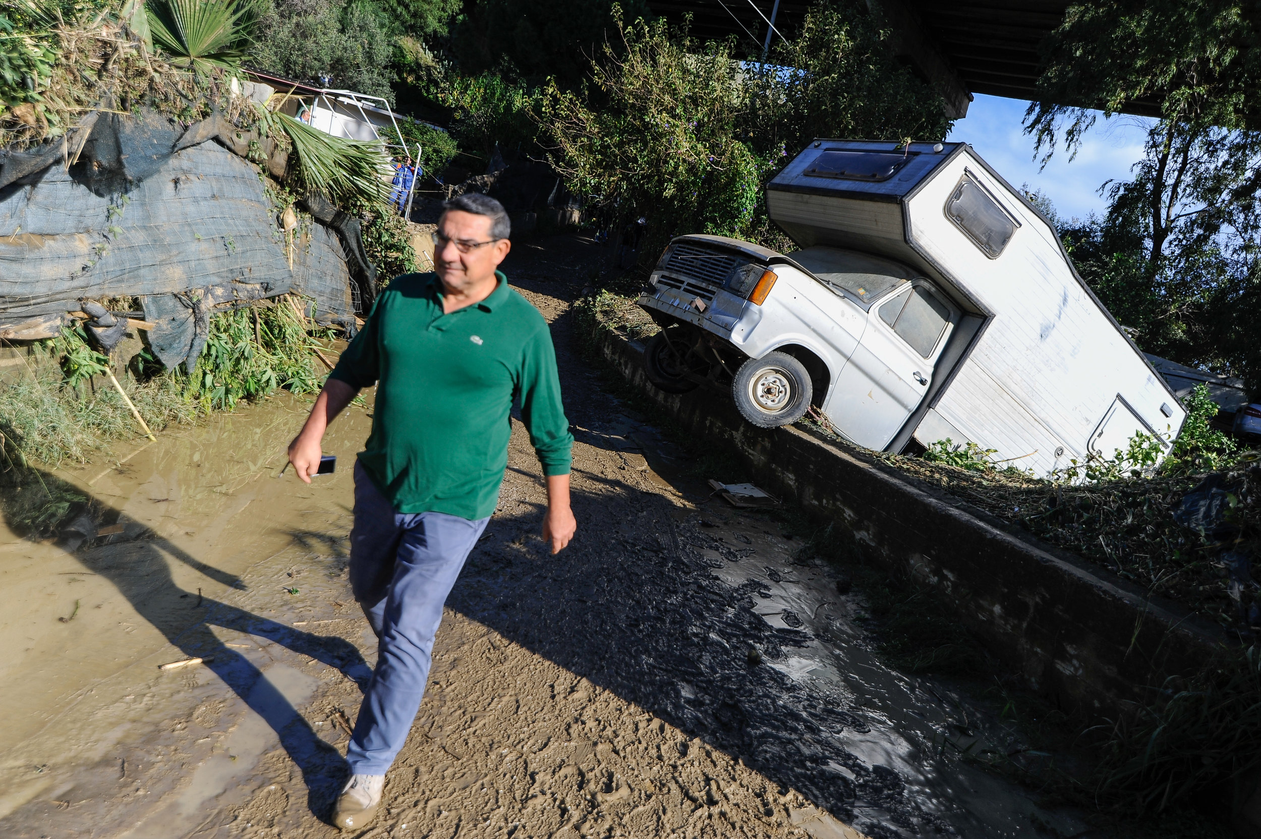 A man walks past a damaged motorhome after the river Milicia flooded causing the death of 9 people in Casteldaccia near Palermo, Italy, November 4, 2018.