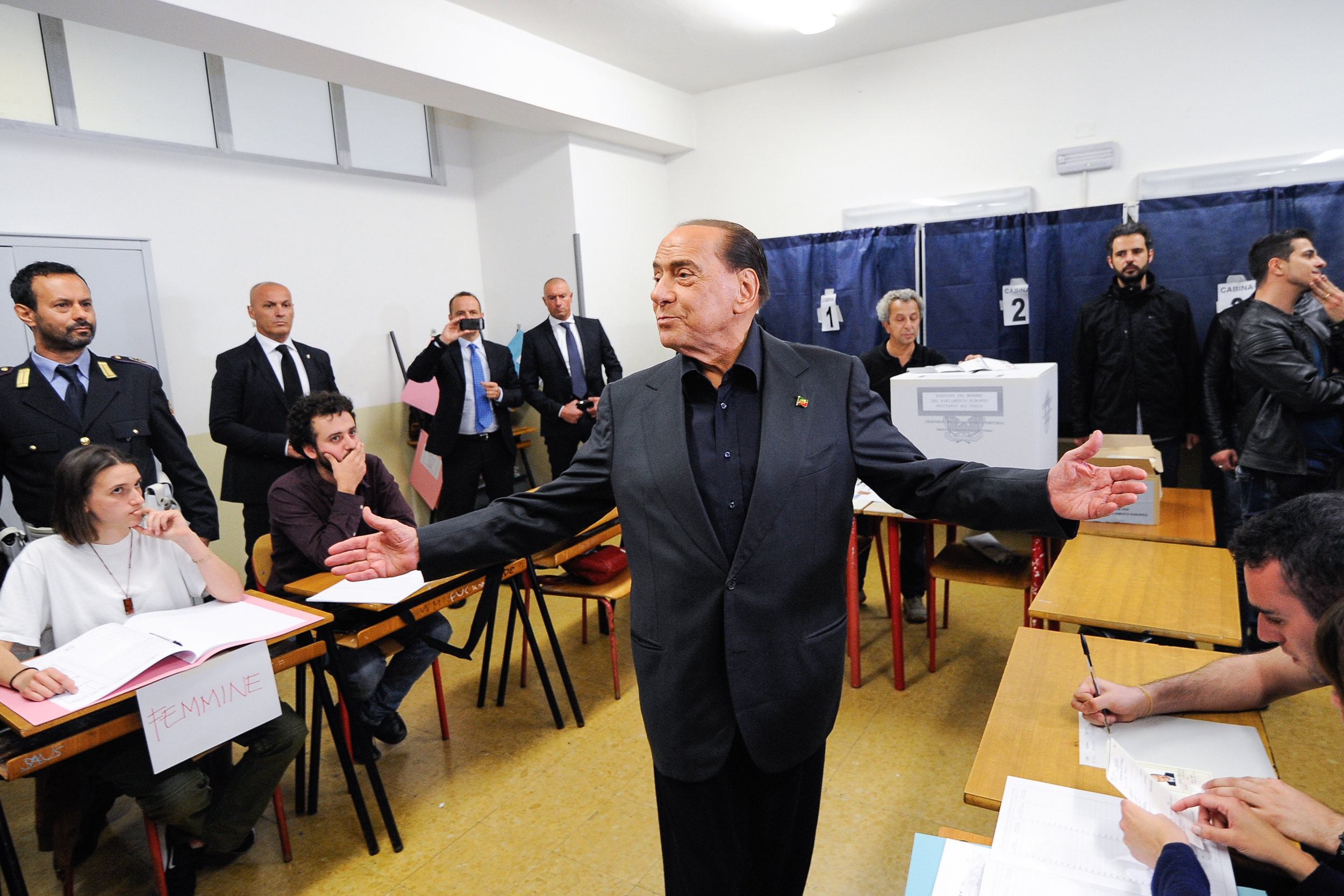 Polling station staff look on as Silvio Berlusconi, former Italian prime minister and leader of Forza Italia (Go Italy!) party, gestures near the registration tables during the European Parliament election in Milan, Italy May 26, 2019.