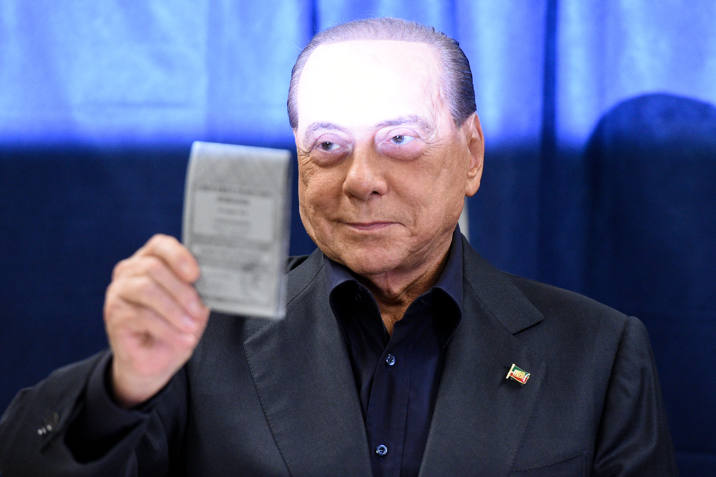 Silvio Berlusconi, former Italian prime minister and leader of Forza Italia (Go Italy!) party, shows his ballot at a European Parliament election polling station in Milan, Italy May 26, 2019.