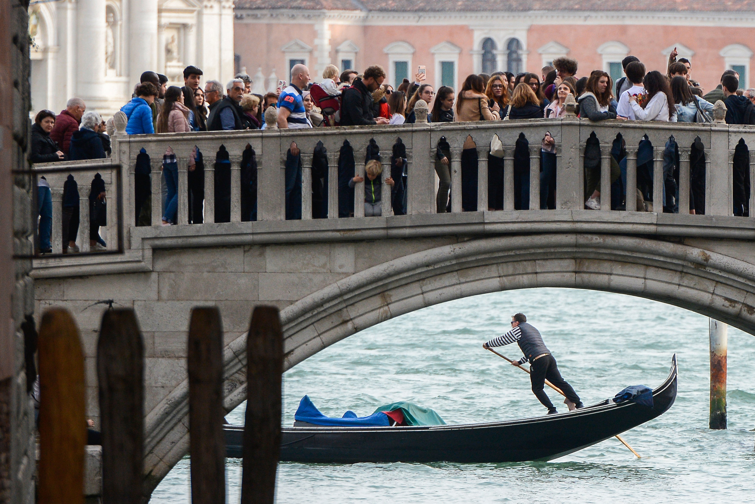 Tourists walk on a bridge as a gondolier rows his gondola near St.Marks Square in Venice, Italy, April 2, 2019.