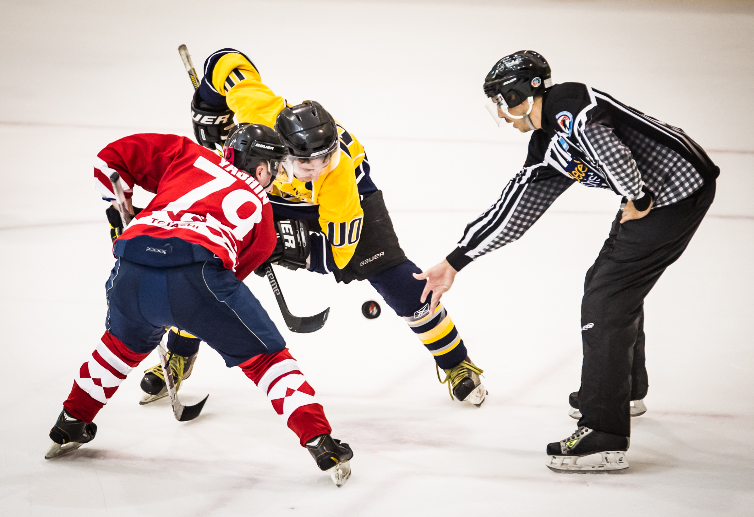 Two players face off as the referee drops the puck during the Lion City Cup at the Rink.