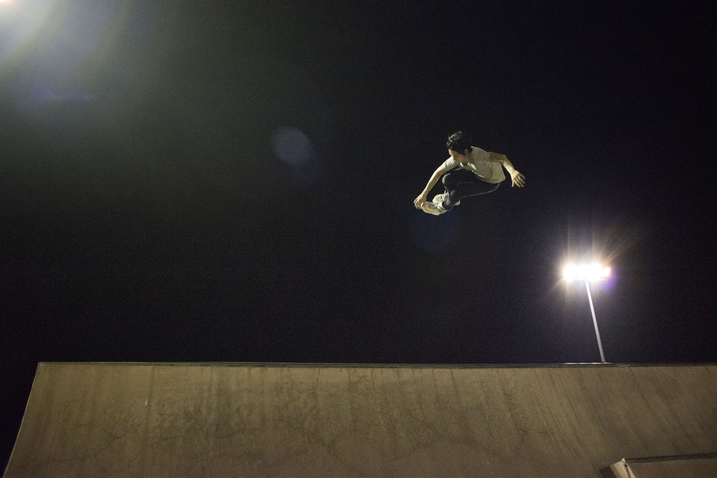 An inline skater executes a grab over the edge of the quarterpipe at the East Coast Skate Park.
