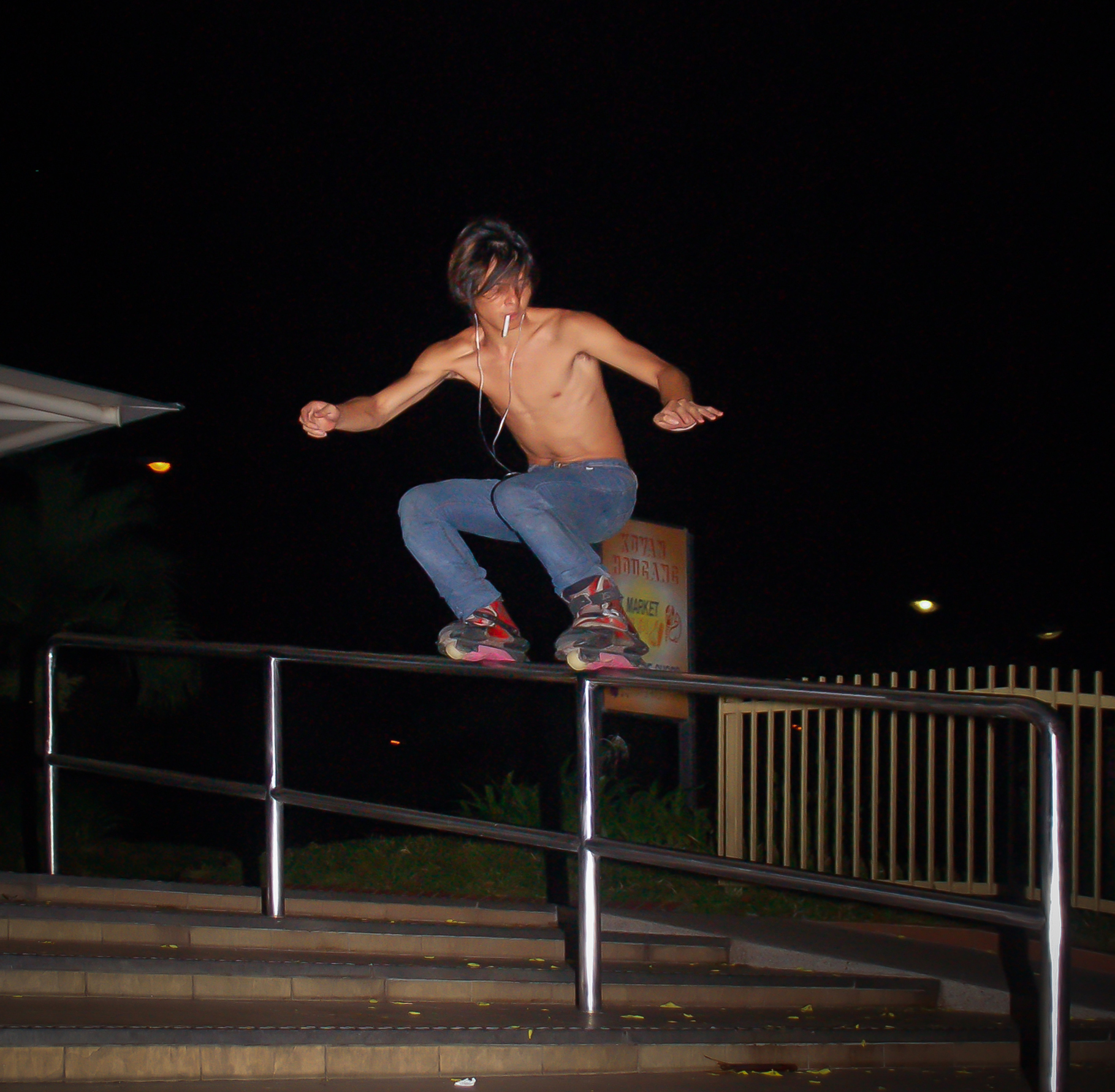 A skater grinds down a handrail while smoking at Hougang Central.